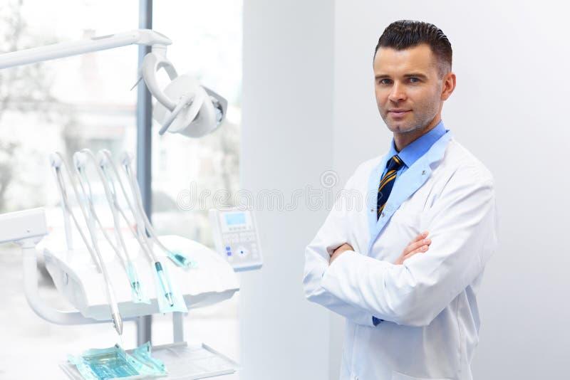 Портрет доктора дантиста Молодой человек на его рабочем месте Зубоврачебное Clin стоковое изображение