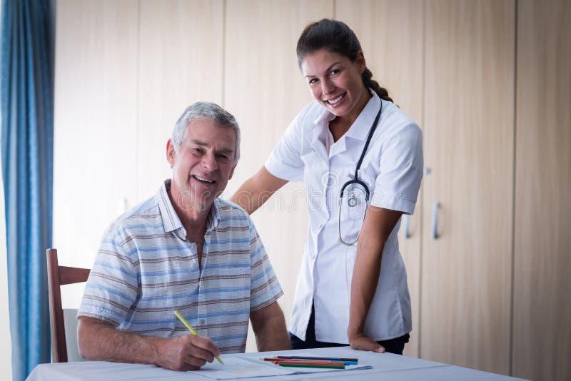 Портрет доктора и старшего человека усмехаясь пока рисующ в книге чертежа стоковые фотографии rf