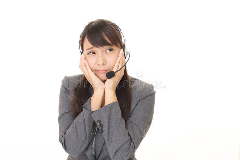 Портрет оператора центра телефонного обслуживания смотря неловкий стоковые фото