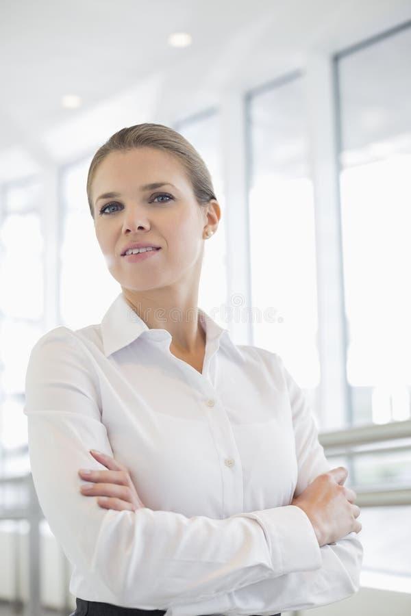 Портрет оружий уверенно коммерсантки стоящих пересек в офис стоковая фотография