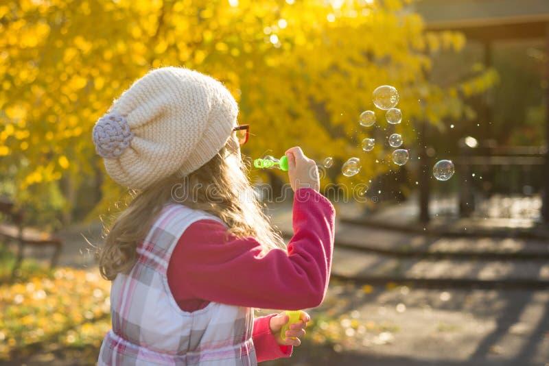 Портрет осени внешний пузырей мыла девушки ребенка дуя стоковая фотография