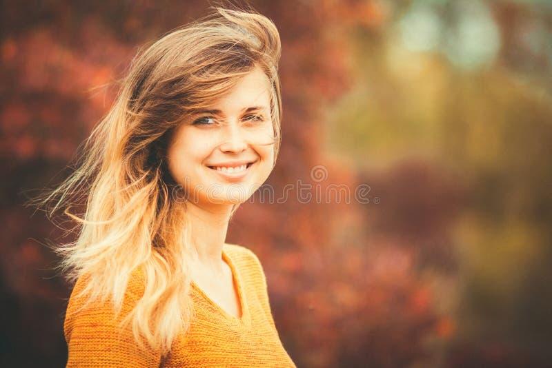 Портрет осени женской стороны против предпосылки оранжевой листвы в парке стоковое фото