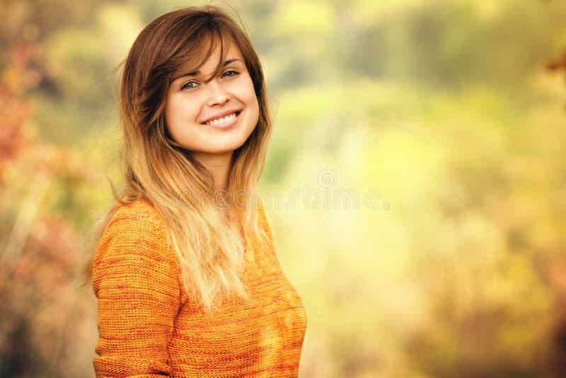 Портрет осени стороны женщины против предпосылки оранжевой листвы в парке стоковые изображения rf