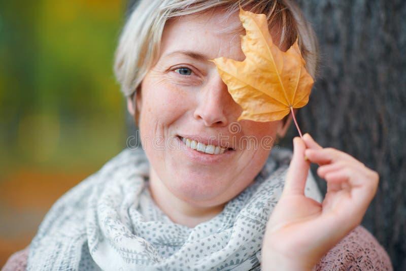 Портрет ослабляя женщины в парке города осени Сидеть около дерева Показывать желтые лист около стороны Яркий солнечный свет и зол стоковое фото