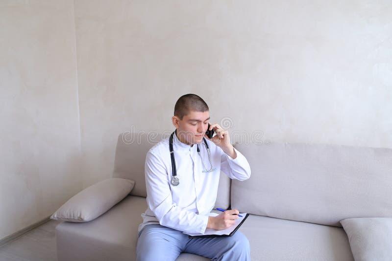 Портрет ответственного мужского доктора который связывает на клетке и стоковые фото