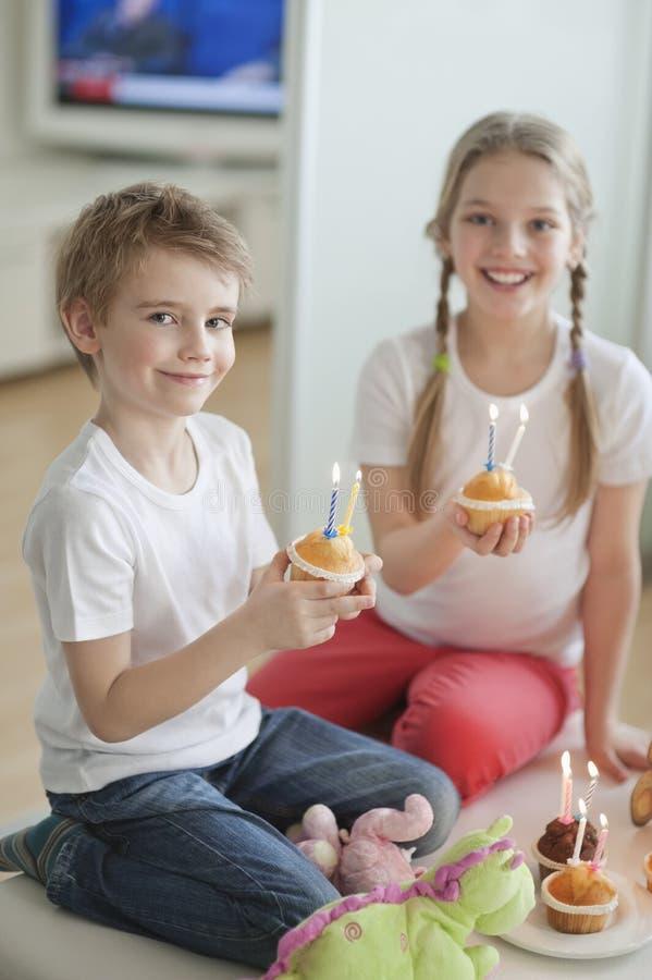 Портрет отпрысков празднуя день рождения с чашкой испечет стоковые изображения rf