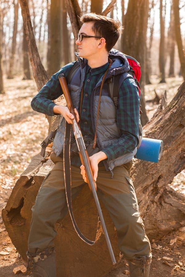 Портрет охотника yang с рюкзаком и оружием на лесе стоковое фото