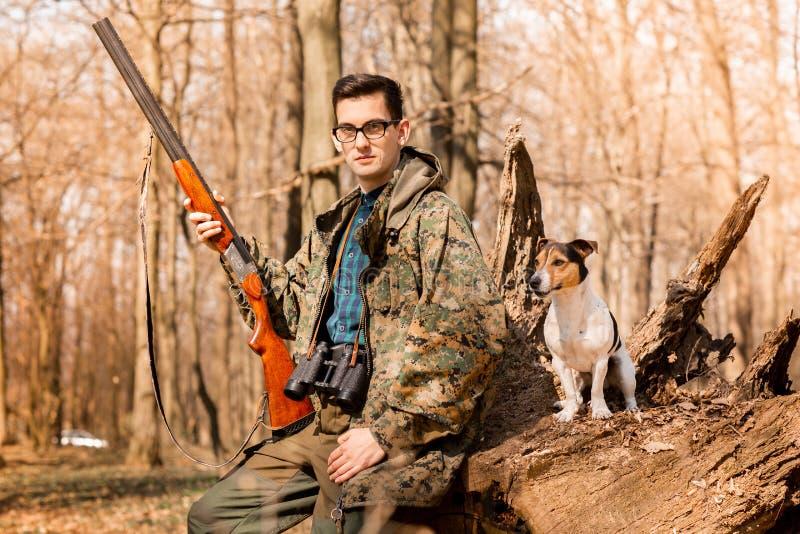 Портрет охотника yang с собакой на лесе стоковое фото