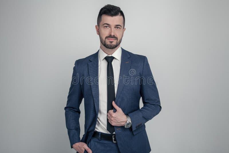 Портрет очаровательного зрелого бизнесмена одетого в костюме представляя пока стоящ и смотрящ камера изолированная над серым цвет стоковые изображения rf