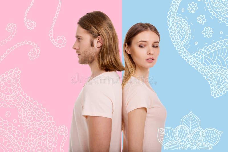 Портрет очаровательной девушки стоя спина к спине с ее парнем стоковая фотография rf