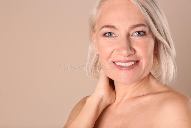 Портрет очаровывать зрелую женщину со здоровой красивой кожей стороны и естественный макияж на бежевой предпосылке, крупном плане стоковое изображение