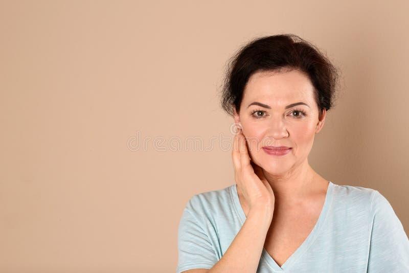 Портрет очаровывать зрелую женщину со здоровой красивой кожей стороны и естественный макияж на бежевой предпосылке стоковое изображение rf