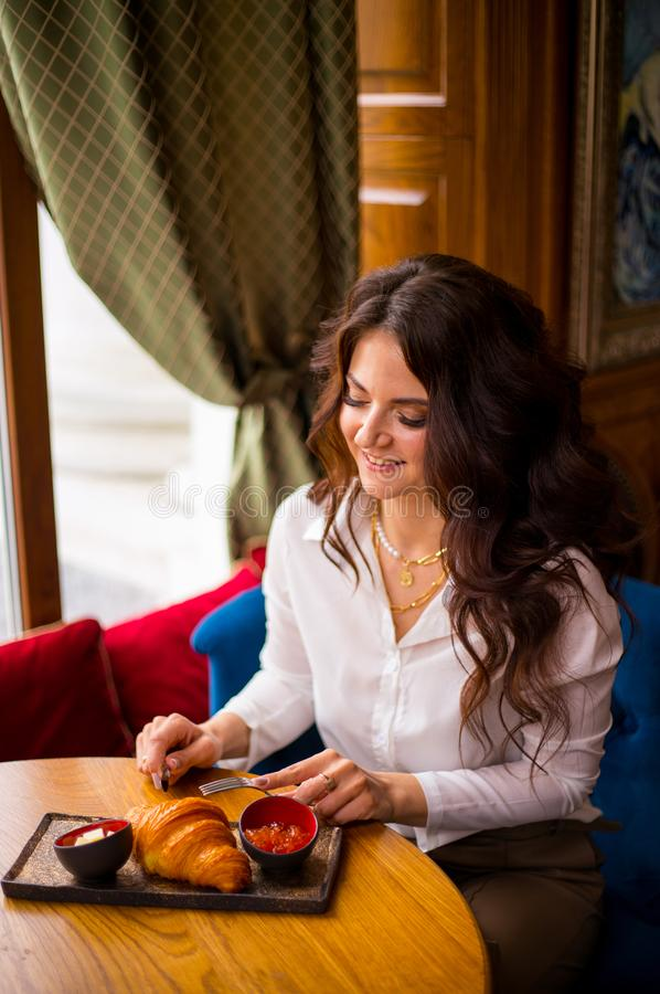 Портрет очаровывая девушки в современной кофейне на завтраке, славном завтраке женщины в кафе есть французские круассаны стоковое изображение