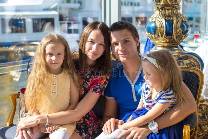 Download Портрет очаровывая красивую семью из четырех человек в ресторане Стоковое Фото - изображение насчитывающей семья, еда: 40587064