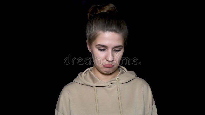 Портрет очень грустной и подавленной молодой женщины изолированной на черной предпосылке Очень грустная, несчастная женщина с реб стоковая фотография