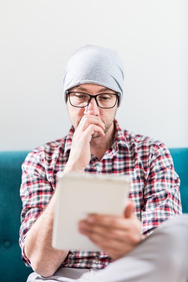 Портрет парня хипстера сидя в софе и смотря цифровой планшет стоковое фото rf