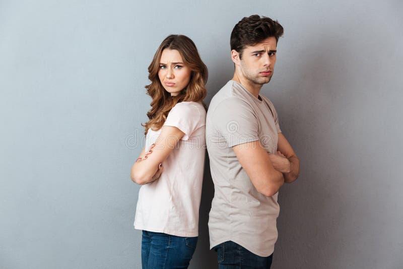 Портрет пары осадки унылой стоя спина к спине стоковые фотографии rf