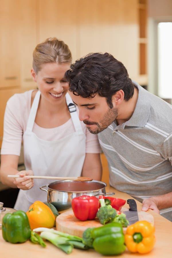 портрет пар счастливый подготовляя соус стоковая фотография rf