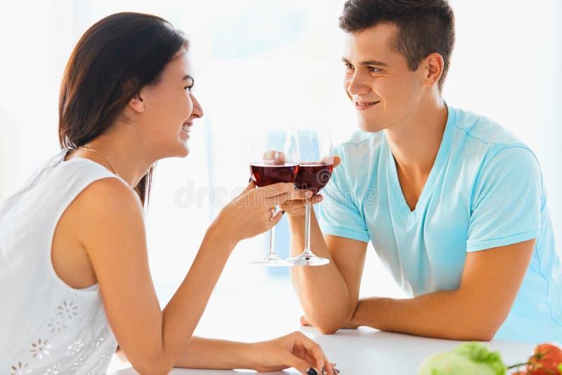 Портрет пар clinking их стекла красного вина в наборе стоковые фото