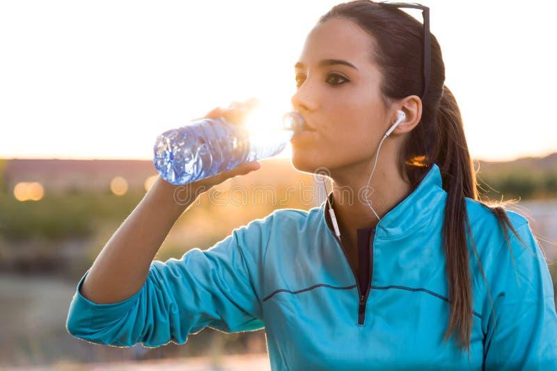 Портрет питьевой воды молодой женщины после бежать стоковое изображение
