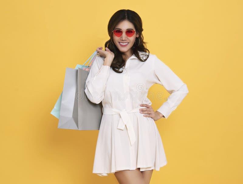 Портрет платья и солнечных очков возбужденной красивой азиатской девушки нося держа хозяйственные сумки изолированный на желтой п стоковое изображение rf