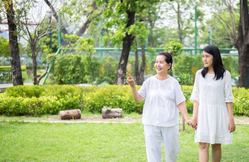 Портрет пожилой азиатской женщины с идти молодых женщин на открытом воздухе совместно в утре, положительной мысли стоковое фото