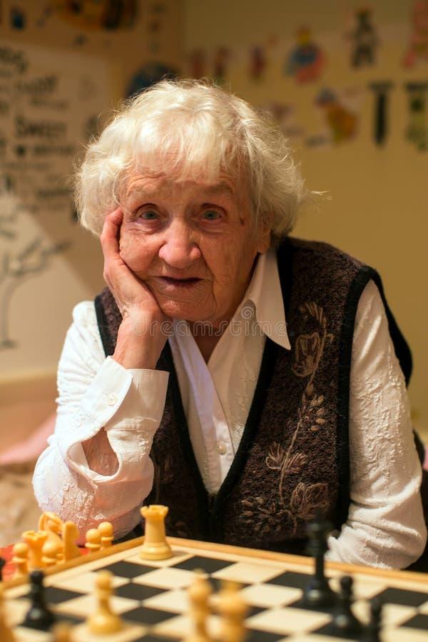 Портрет пожилой женщины играя шахматы хобби стоковая фотография