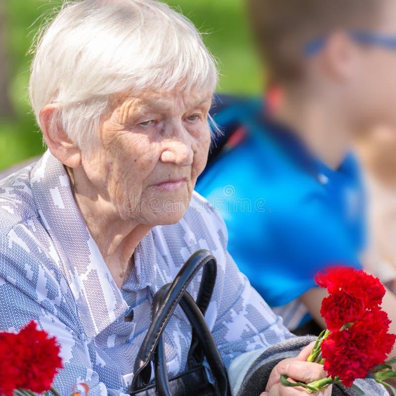 Портрет пожилой женщины с гвоздиками в ее руках 9-ого мая стоковое изображение
