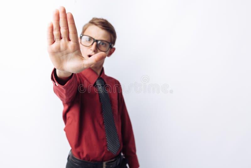 Портрет положительного и эмоционального школьника, представляя и показывая руку стопа, белую предпосылку, стекла, красную рубашку стоковые изображения rf