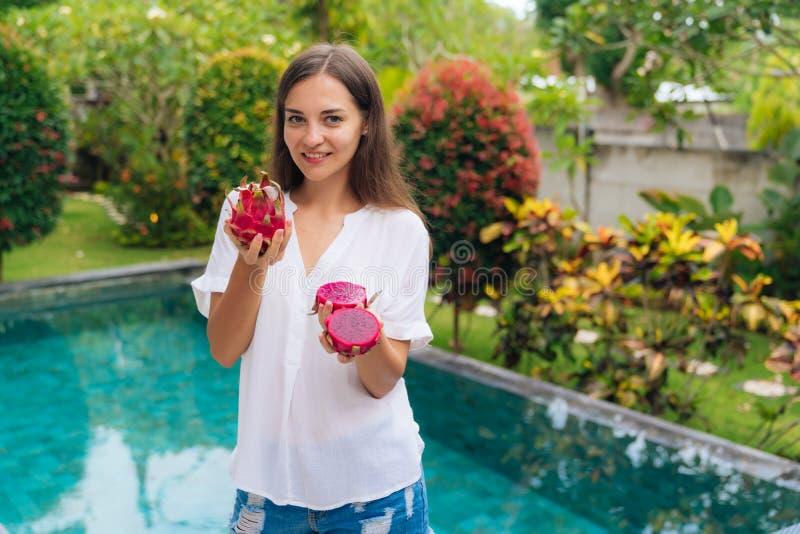 Портрет положительных усмехаясь девушки и плода в ее руках, бассейна дракона на предпосылке стоковая фотография rf