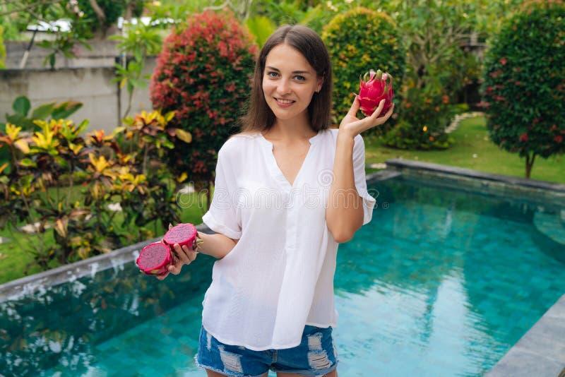 Портрет положительных усмехаясь девушки и плода в ее руках, бассейна дракона на предпосылке стоковое фото