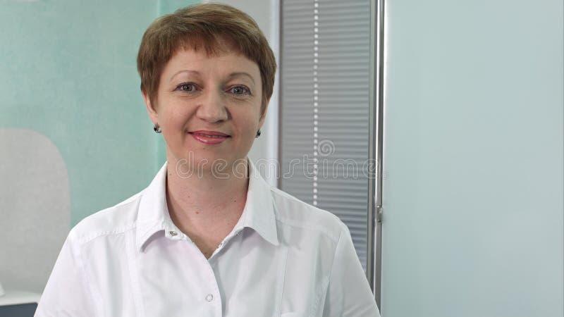 Портрет постаретого женского доктора на коридоре больницы смотря усмехаться камеры стоковое фото rf