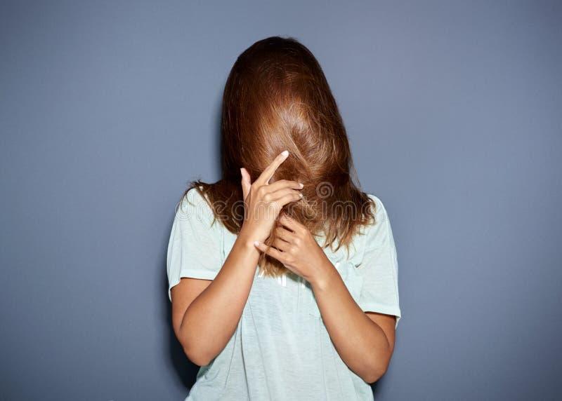 Портрет потехи женщины пряча за ее волосами стоковые фото