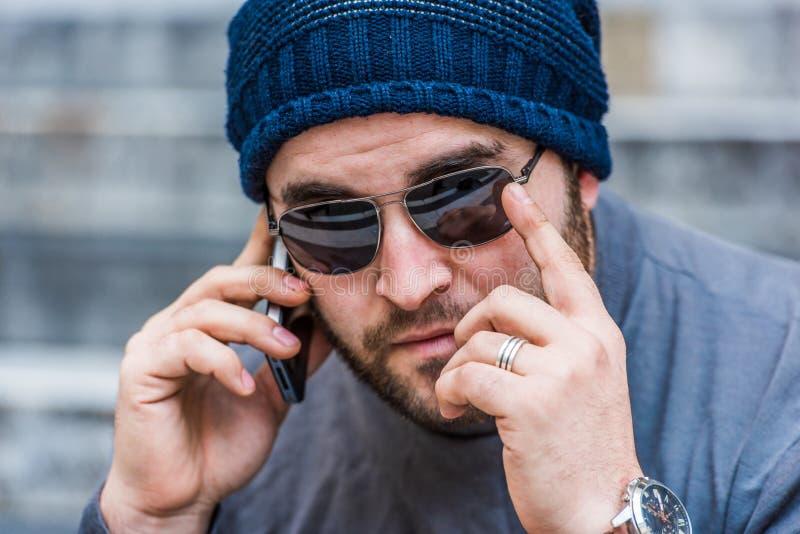 Портрет потревоженного человека с солнечными очками говоря на телефоне - смотреть камеру стоковые изображения