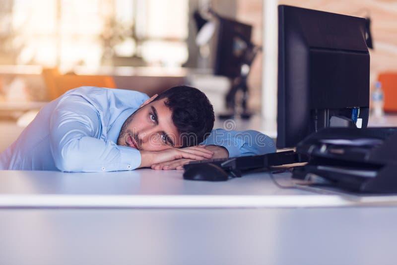 Портрет подавленного работника офиса кладя на его стол и думать стоковая фотография
