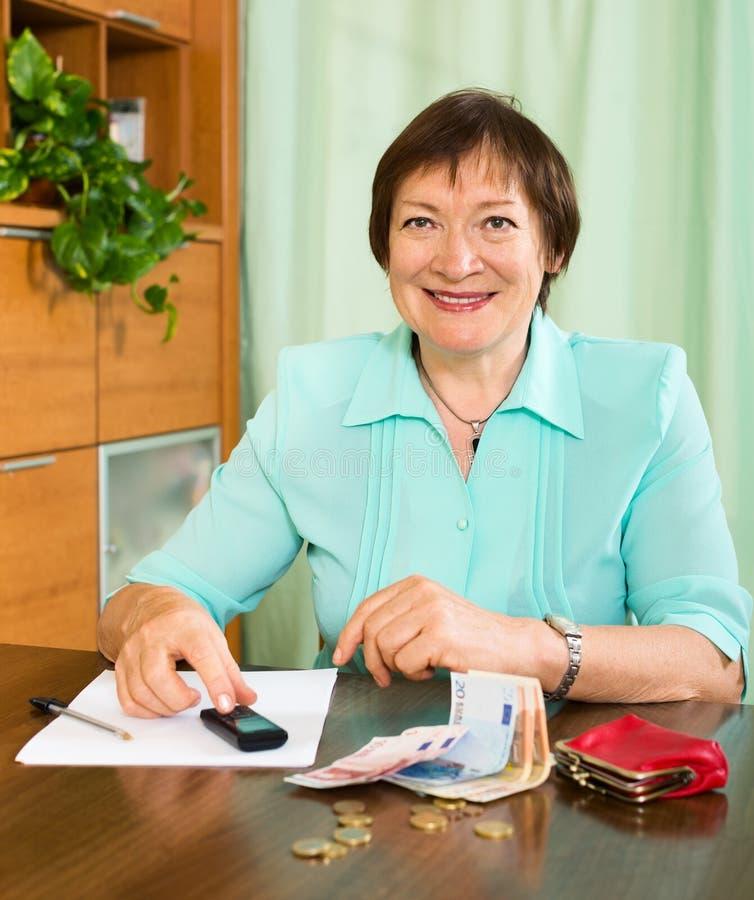 Портрет положительного женского пенсионера с наличными деньгами и счетами стоковые изображения rf