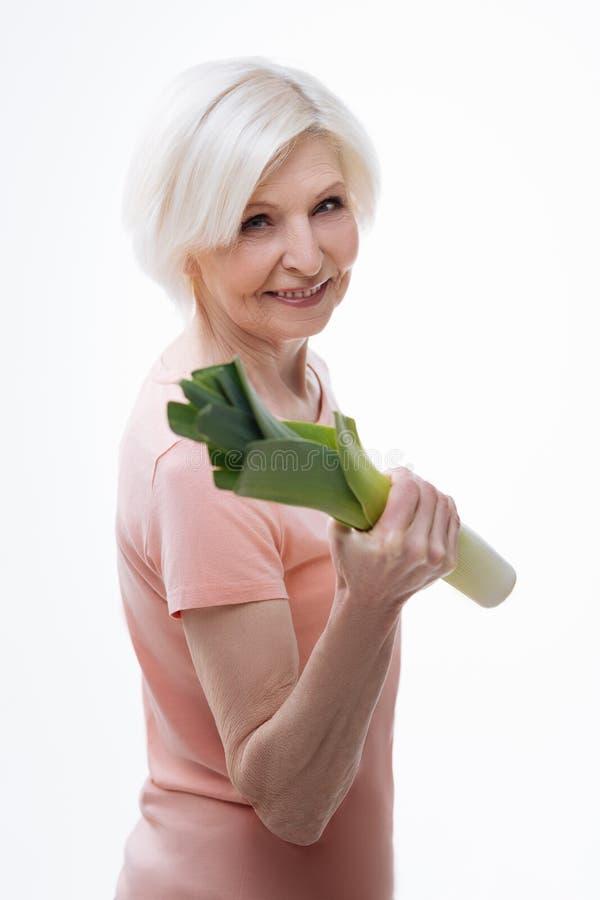 Портрет положительной милой женщины держа лук-порей в руке стоковые изображения rf