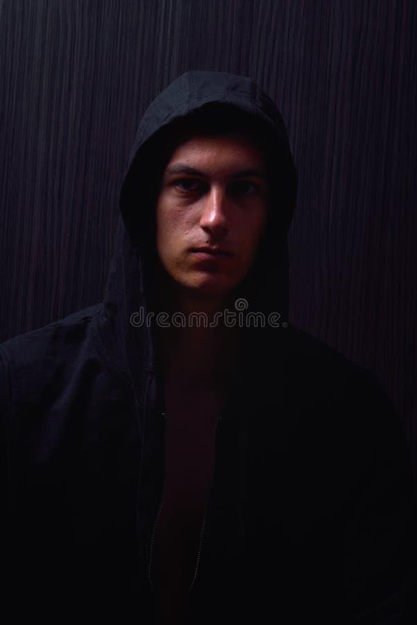 Портрет подростка с серьезным выражением и черным hoodie стоковое фото rf