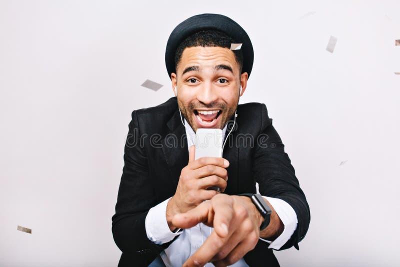 Портрет празднуя партию караоке возбужденного красивого парня в костюме, шляпе имея потеху на белой предпосылке Модный взгляд стоковые изображения rf