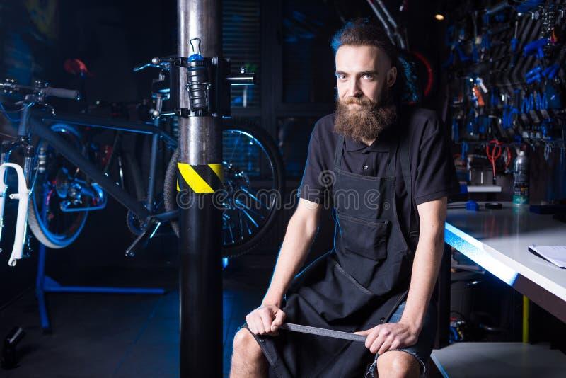 Портрет предпринимателя мелкого бизнеса молодого человека с бородой Работник мастерской механика велосипеда Гая сидя с инструмент стоковая фотография rf