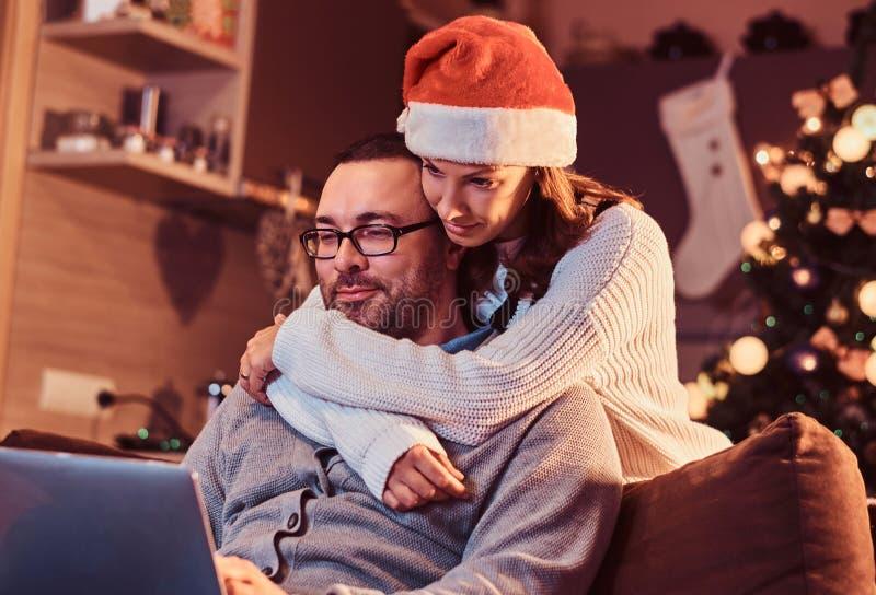 Портрет прелестной пары - очаровательная женщина в шляпе Санты обнимая ее человека и используя компьтер-книжку стоковые фото