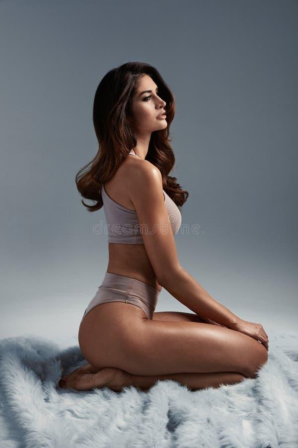 Портрет прелестной, смуглой женщины сидя на одеяле стоковое фото rf