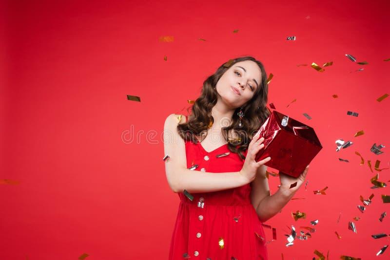 Портрет прелестной усмехаясь молодой женщины с длинным вьющиеся волосы представляя на красной предпосылке студии стоковые изображения rf