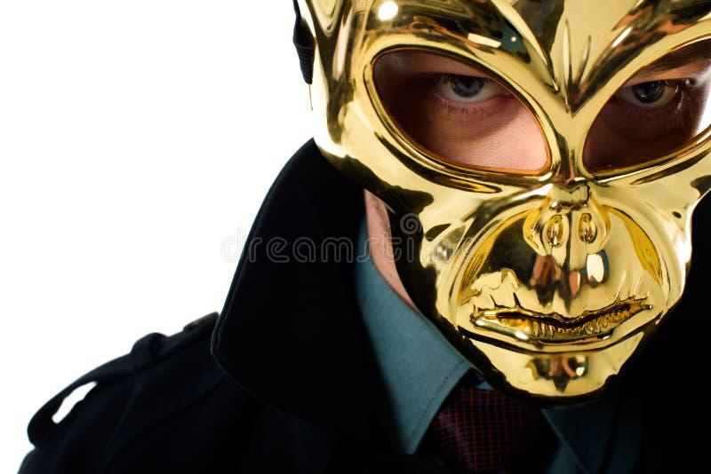 портрет преступника в золотой маске и черном пальто смотря камеру стоковое фото
