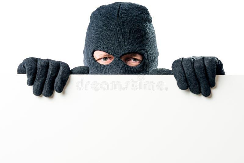 Портрет преступника в маске с большим плакатом стоковое фото rf