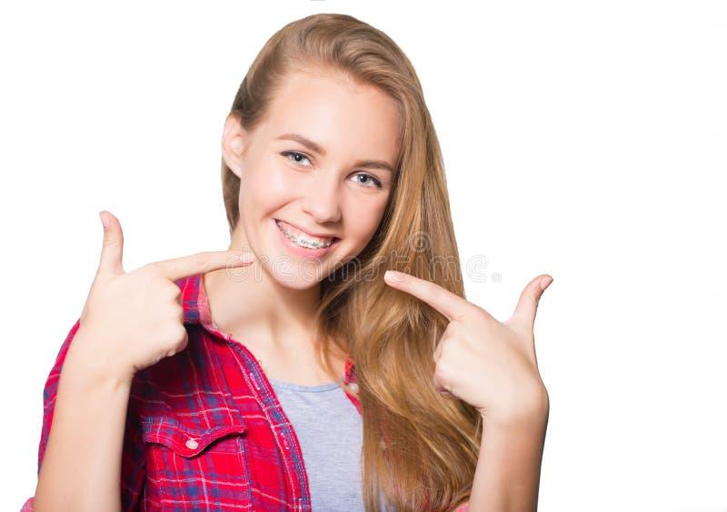 Портрет предназначенной для подростков девушки показывая зубоврачебные расчалки стоковая фотография