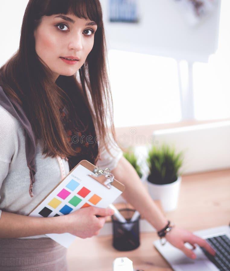 Портрет привлекательного женского модельера сидя на столе офиса стоковое изображение rf