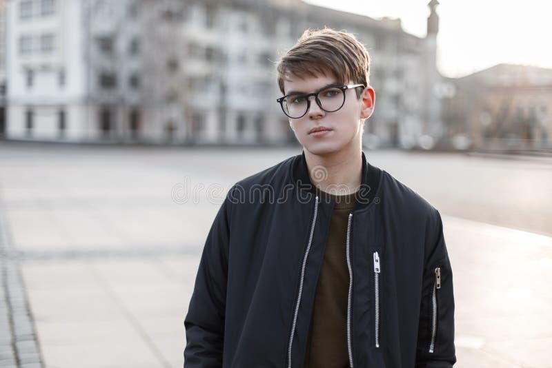 Портрет привлекательного молодого мужчины хипстера в стеклах с модным стилем причесок в стильном outerwear стоковое фото rf
