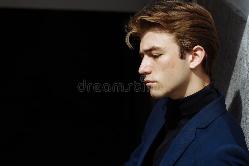 Портрет привлекательного молодого человека в голубом костюме в городе Человек в профиле стоковое фото