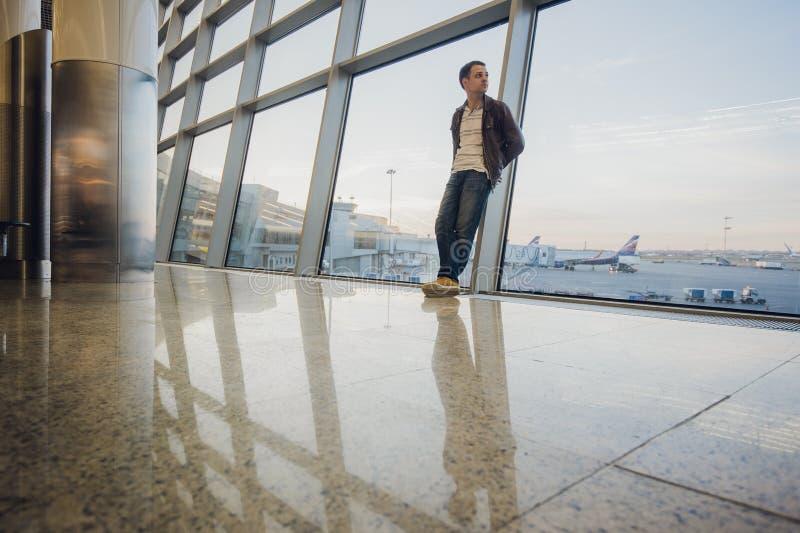 Портрет привлекательного молодого человека идя и смотря мобильный телефон стоковые фото